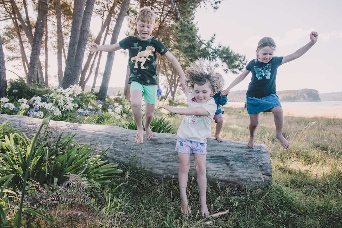 4 happy children jumping off a log