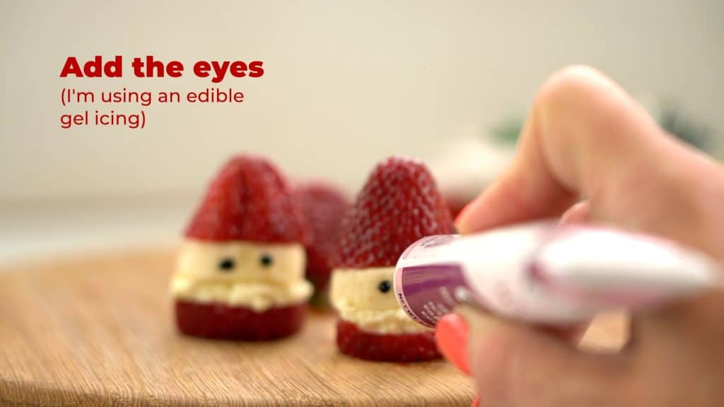 hand holding gel icing drawing eyes onto a strawberry Santa.