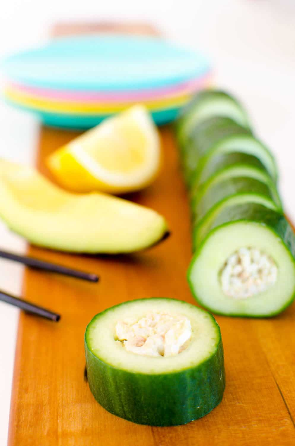 Pieces of cucumber sushi on a wooden board with a set of chopsticks