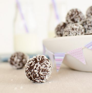 Coconut covered chocolate bliss ball in front of a bowl of bliss balls ready for a party