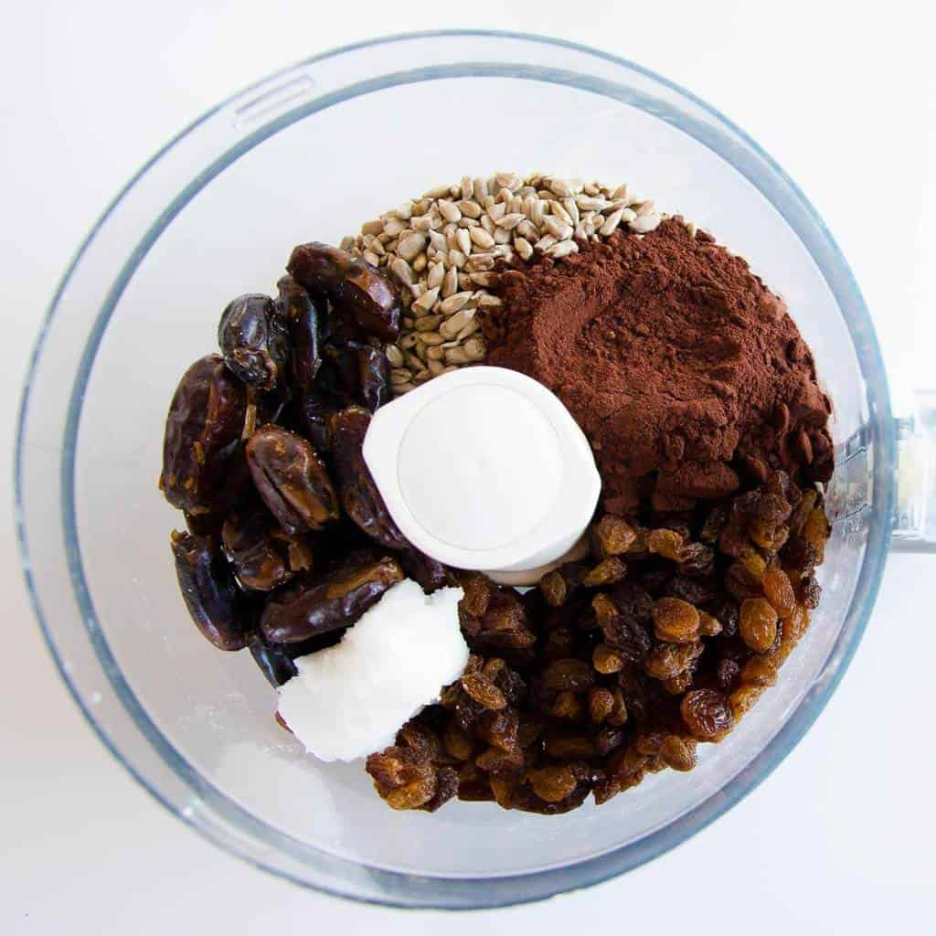 Ingredients for chocolate bliss balls in a food processor, sunflower seeds, dates, cocoa, sultanas, coconut