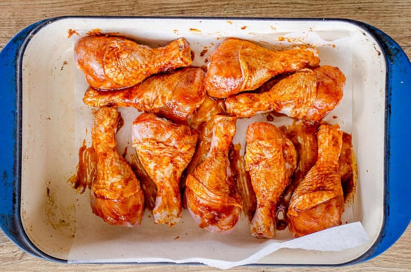 Marinated paprika chicken drumsticks in a blue baking dish ready to bake