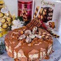 A delicious triple layer Christmas chocolate hazelnut ice-cream cake! Chocolate, vanilla and hazelnut flavoured ice-cream layers packed full of Christmas treats, Ferrero Rocher, Guylian Chocolates and More