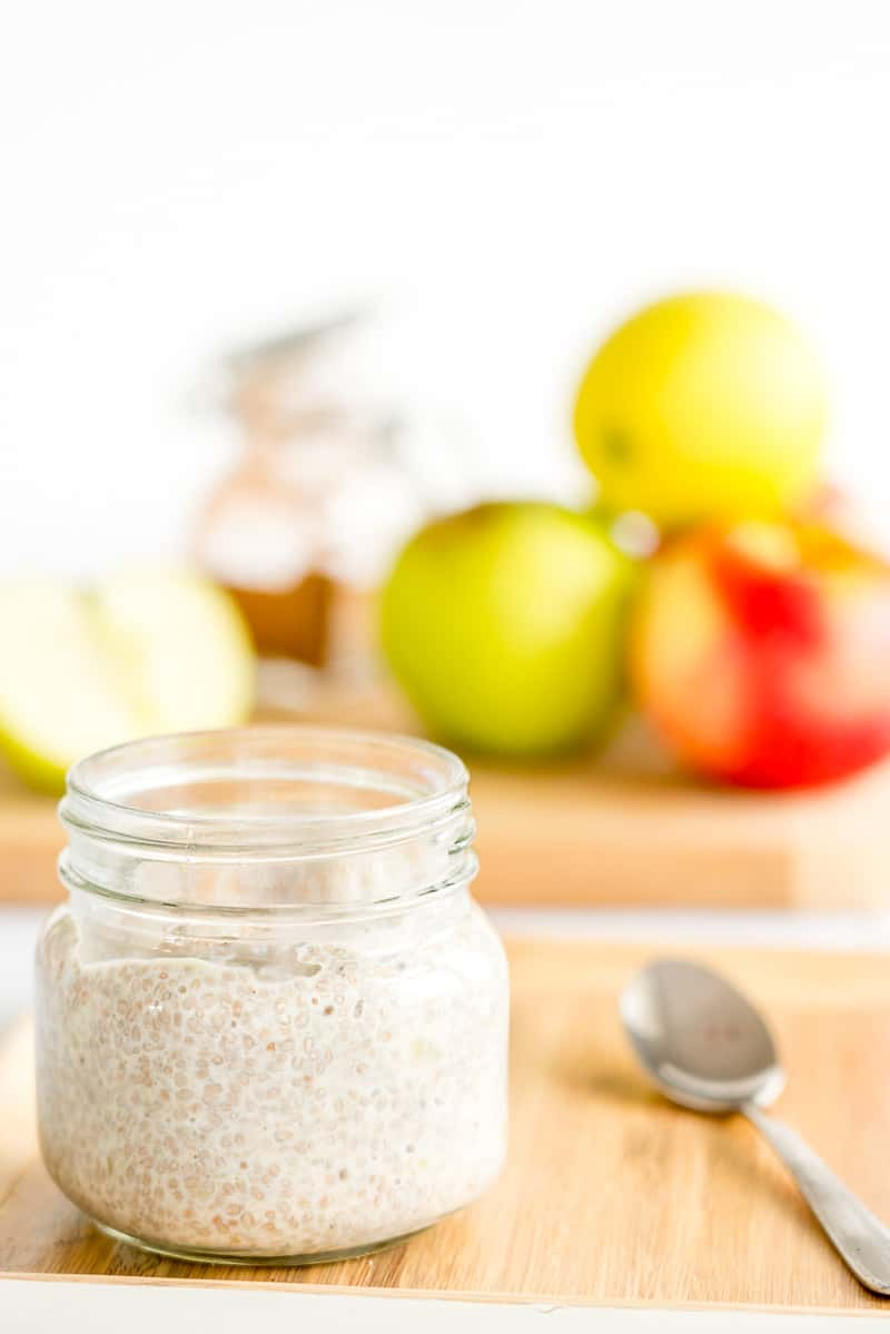 jar of apple pudding with a spoon next to it, apples in the background