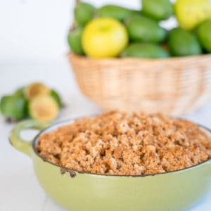 Apple Feijoa & Almond Crumble in a green baking dish, basket of fruit in the background