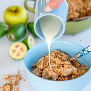 Apple Feijoa and Almond Crumble in a Blue Bowl with vanilla custard being poured over it