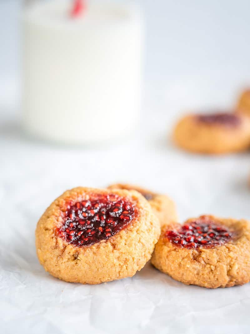 Peanut Butter and Jam Thumbprint Cookies, close up of three cookies on a white surface