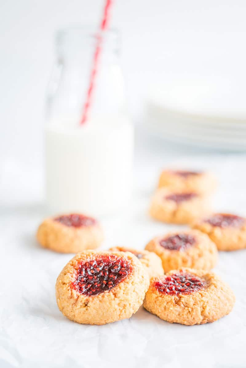 Peanut Butter and Jam Thumbprint Cookies a pile of cookies with a bottle of milk in the backgrounf