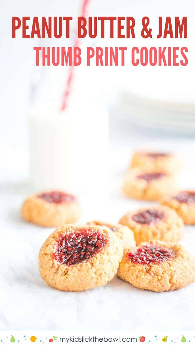 Peanut butter and Jam Thumbprint Cookies on a white table with a bottle of milk and white side plates