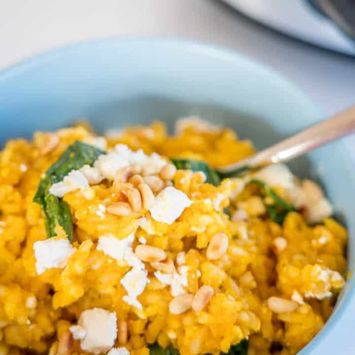 Slow Cooker Risotto, in a blue bowl topped with feta and pinenuts
