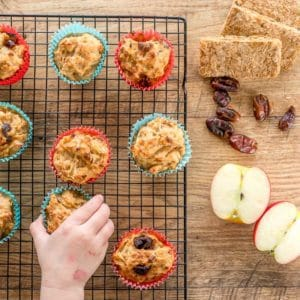apple and date muffins on a cooling rack, child's hand reaching out to grab one