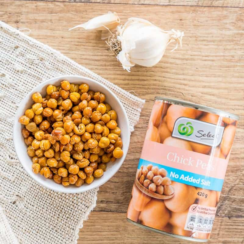 Crunchy roasted chickpea in a white bowl, with a whole clove of garlic and a tin of chickpeas