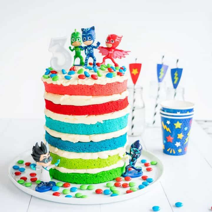 colourful layered birthday cake filled with butter cream, topped with pj masks characters