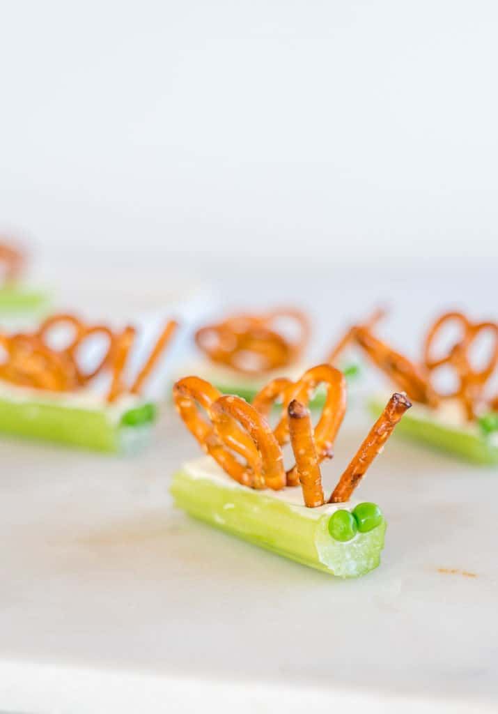 celery sticks filled with cream cheese, topped with pretzles to create butterfly wings and peas for eyes.