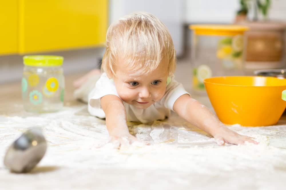 Cooking with kids is messy, Little boy child laying on very messy kitchen floor. Toddler covered in white baking flour.