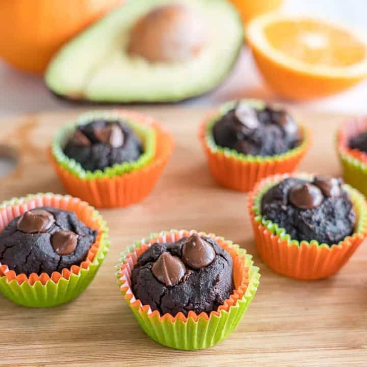 Avocado muffins on a wooden chopping board oranges and avocado in background