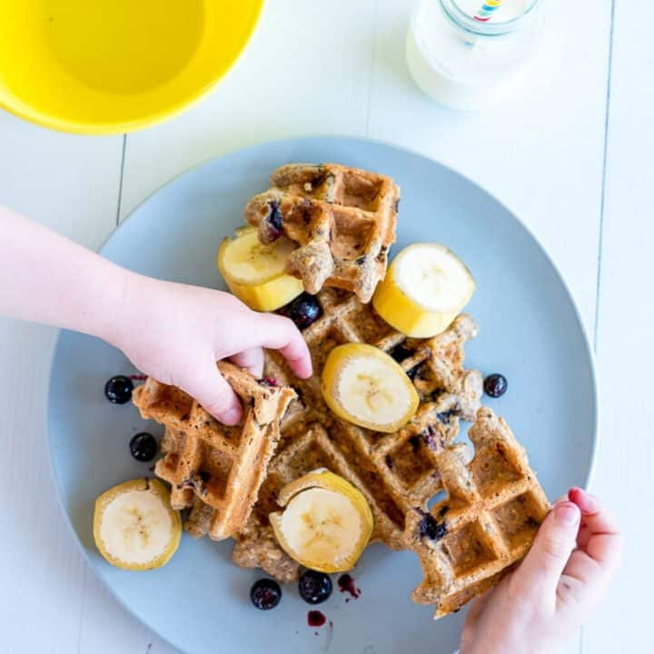waffles on a plate, with banana and blueberries, 2 children's hands reaching for the waffles
