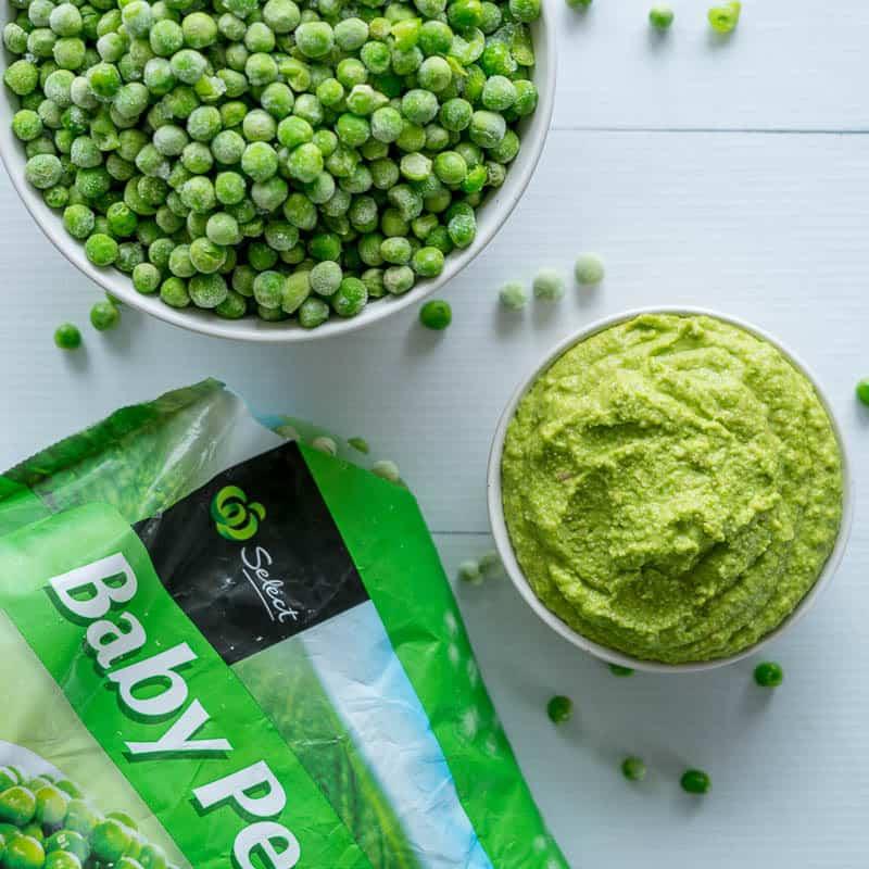 Pea pesto in a small bowl with frozen peas