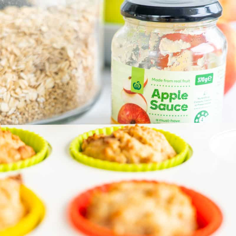 Healthy apple cinnamon muffins with jar of apple sauce in the bacjground