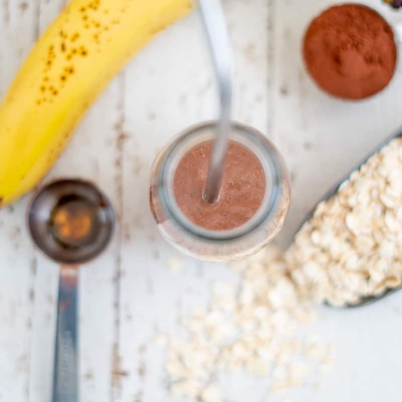 Healthy homemade chocolate milk ingredients, oats, cocoa, banana, maple syrup and milk