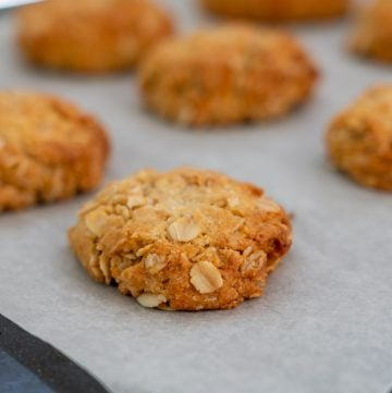 cooked anzac biscuit on baking paper lined tray