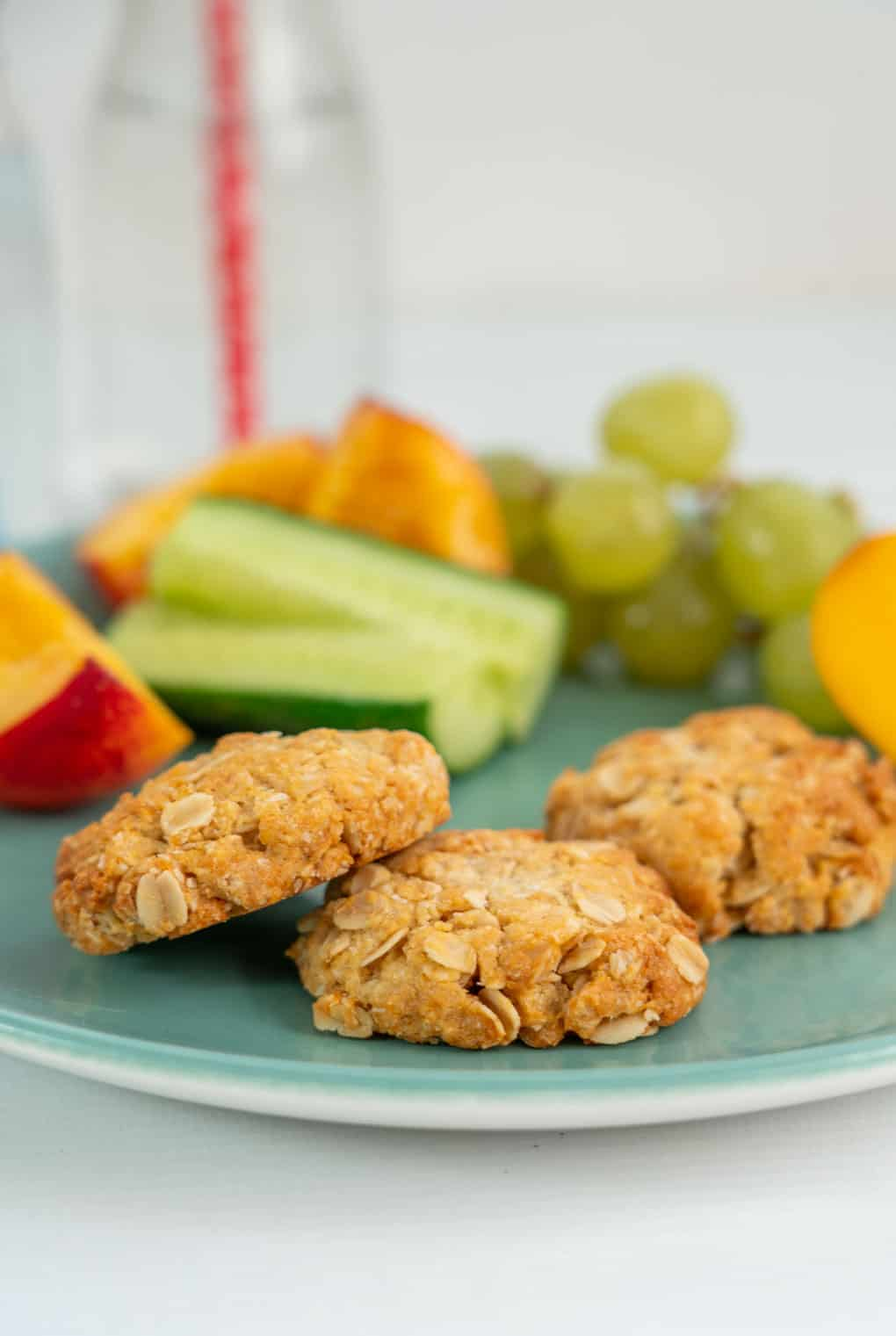 Snack plate of anzac biscuits with fruit and vegetables