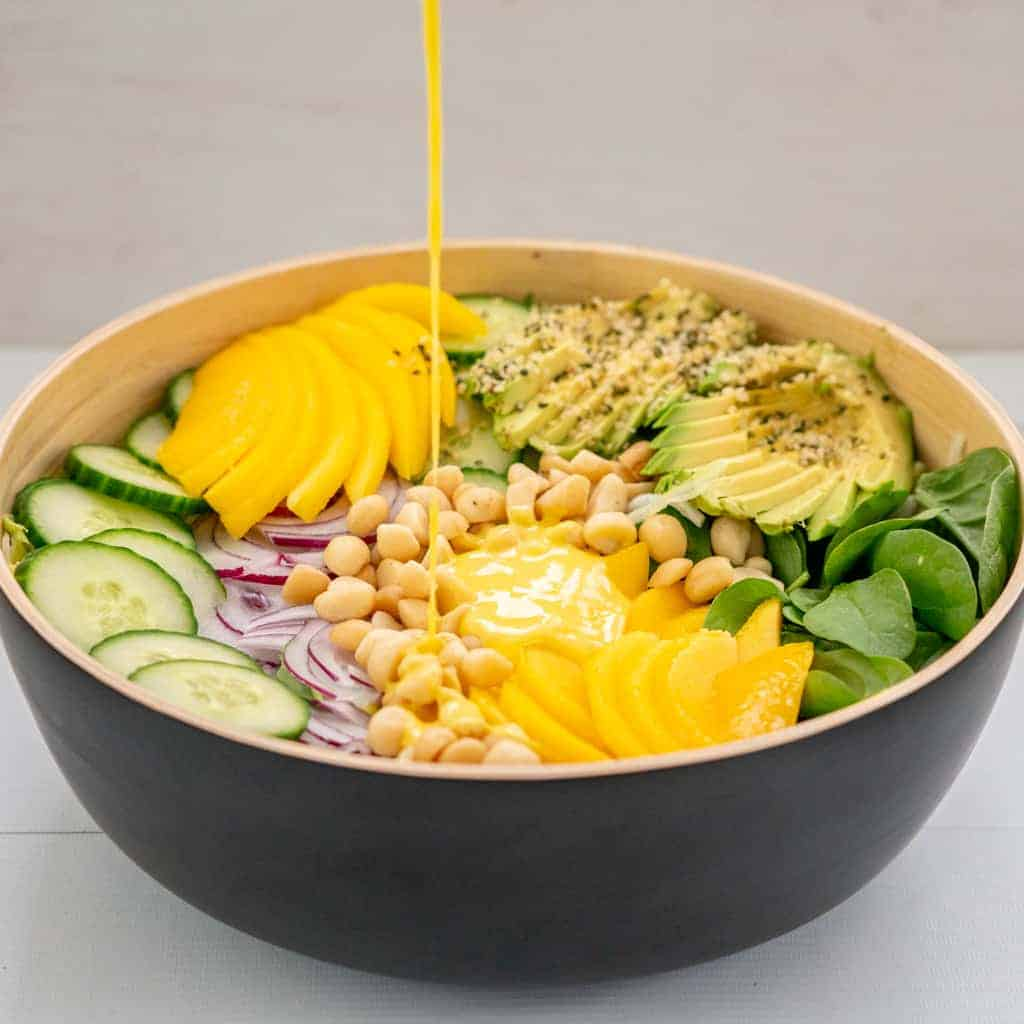 Mango salad dressing being drizzled onto a colourful salad