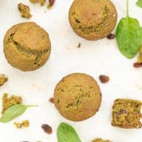 Green muffins on a white bench top which is scattered with raisins and spinach leaves.