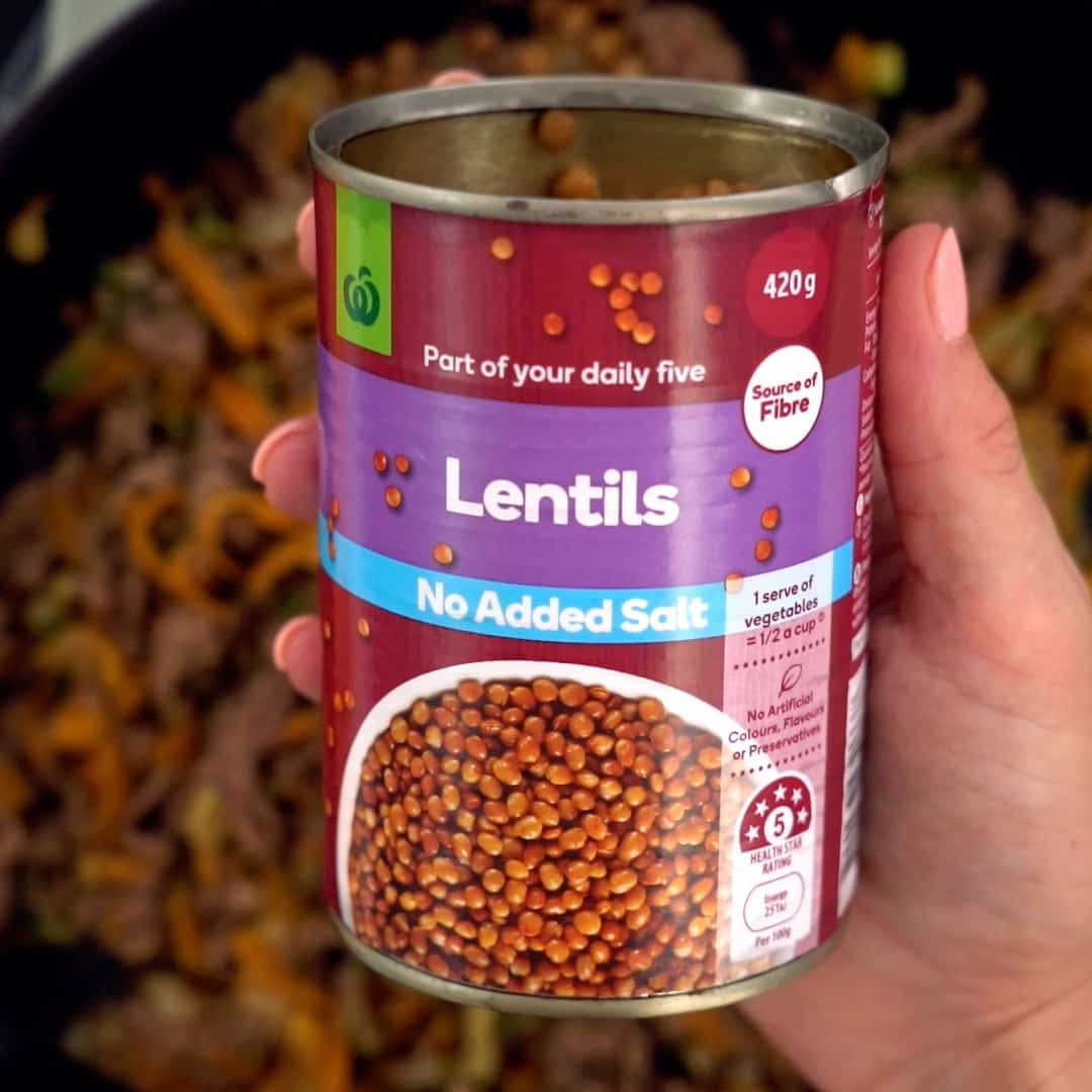 hand holding a can of lentils above a pan of minced beef