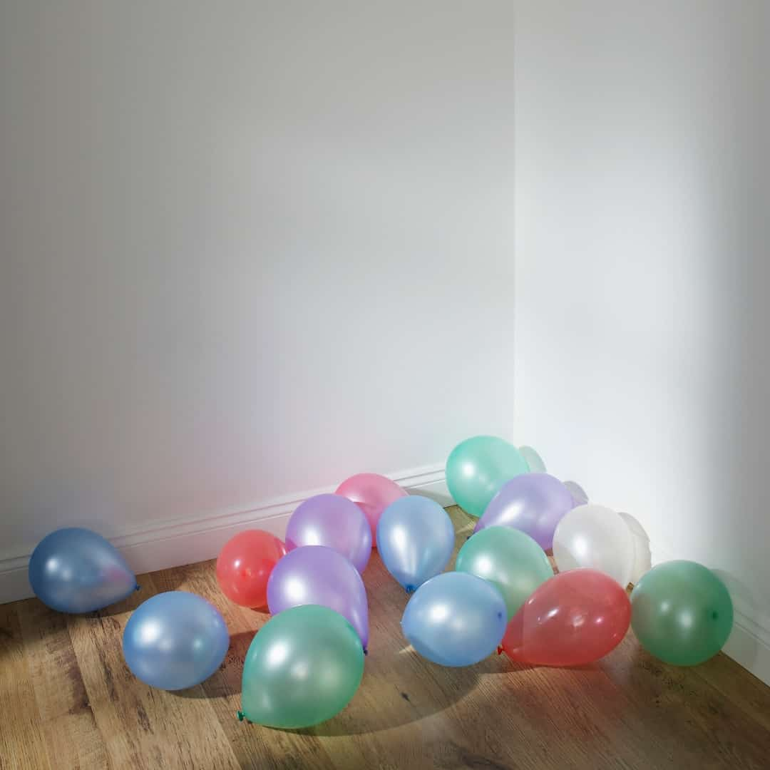 balloons on the floor in the corner of a living room
