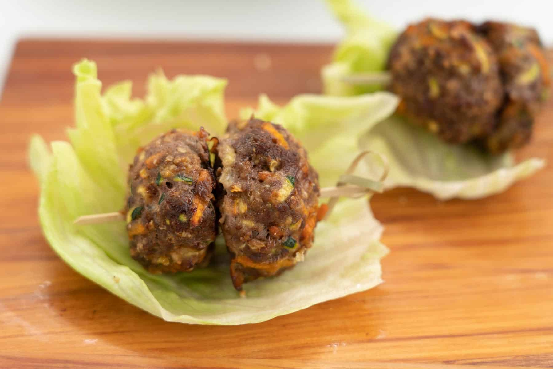 2 plain rissoles on a small bamboo skewer sitting on a lettuce leaf