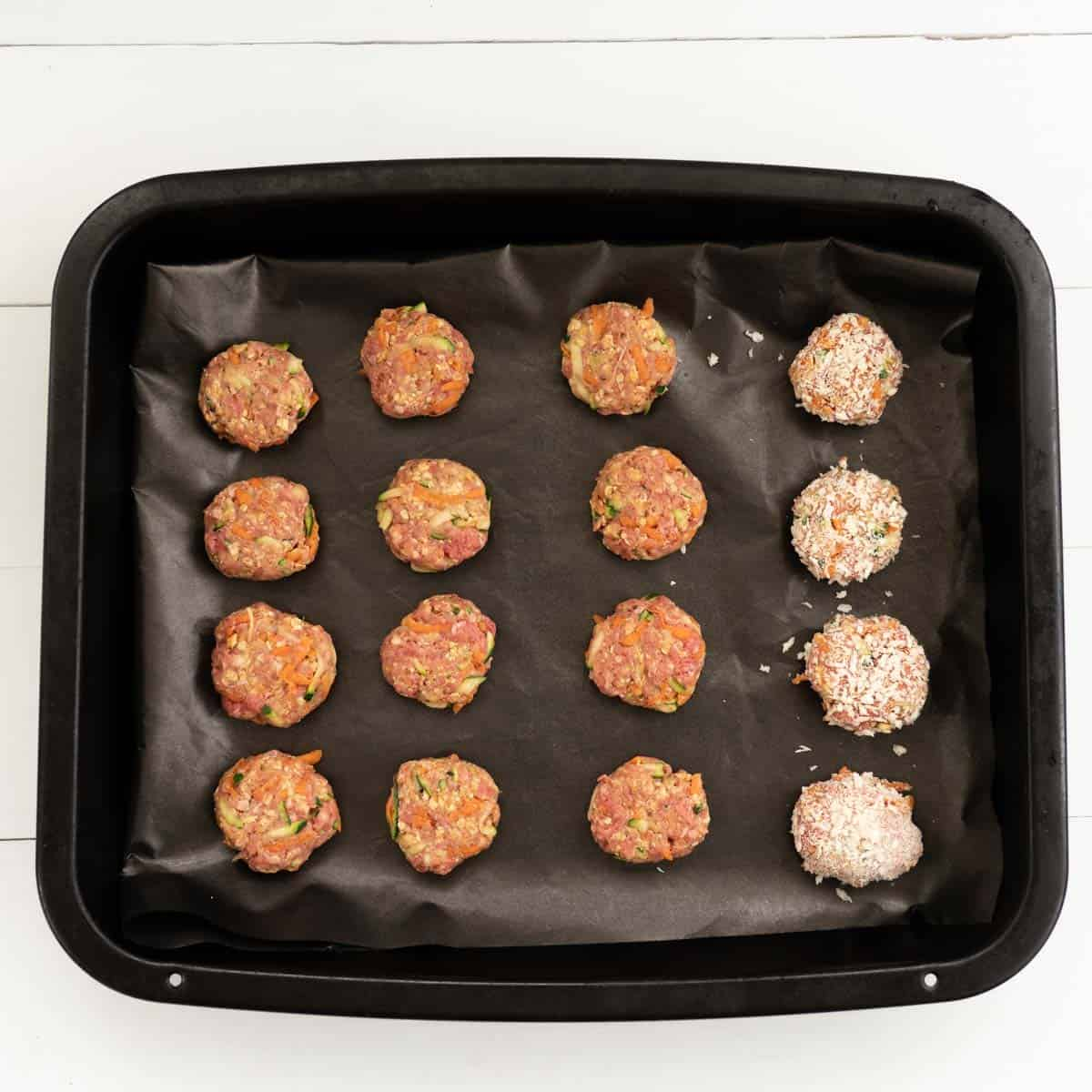 Tray of rissoles ready to go into the oven, 12 are plain and 4 are crumbed
