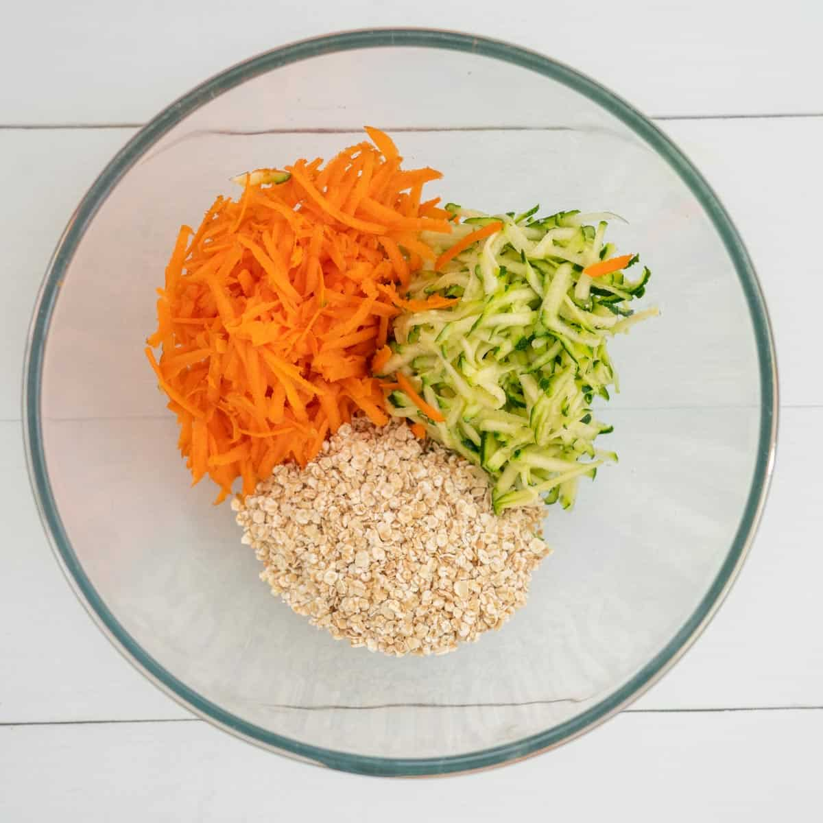 Mixing bowl with grated carrot, grated zucchini and oats
