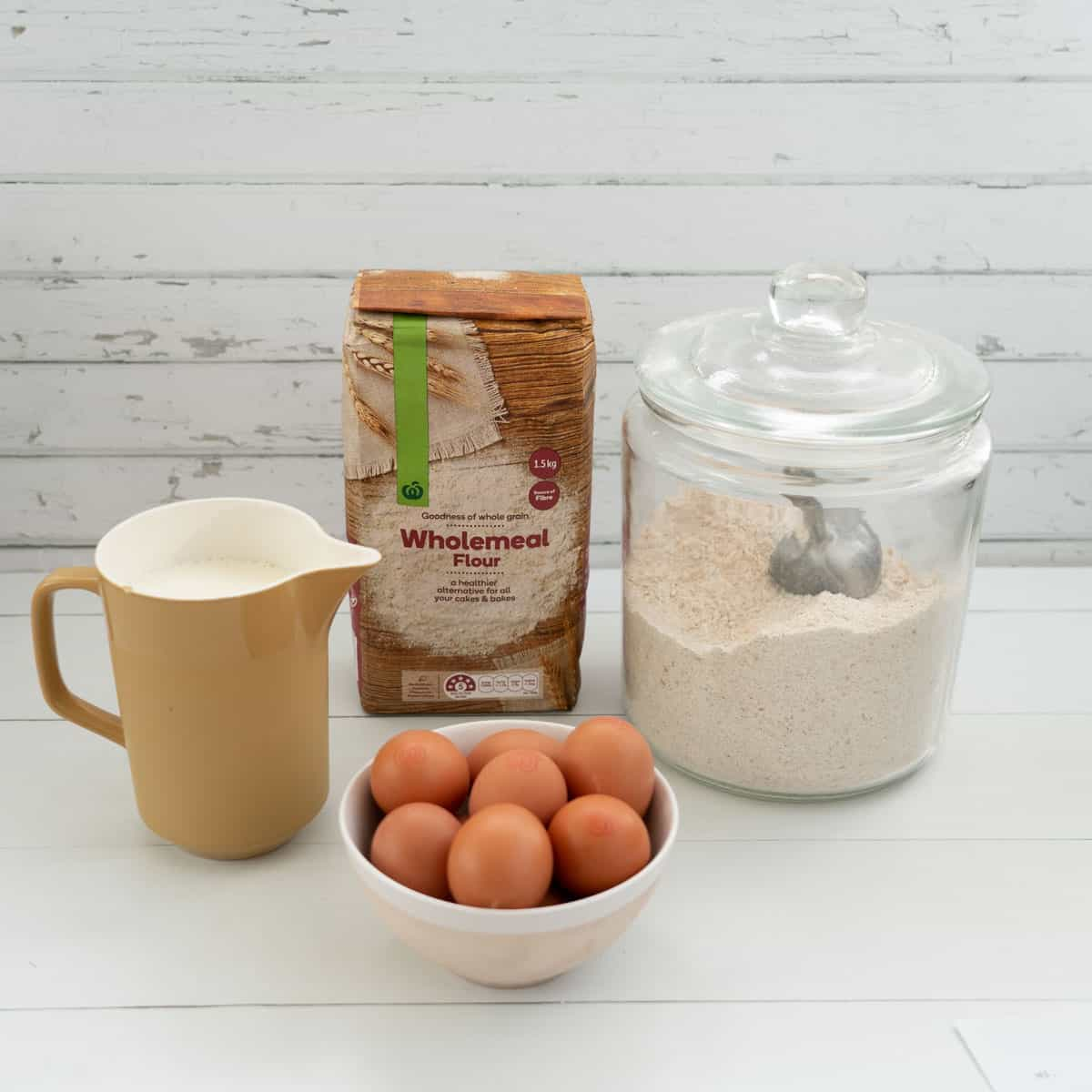 jug of milk, bowl of eggs, bag of wholemeal flour and large glass flour jar with scoop