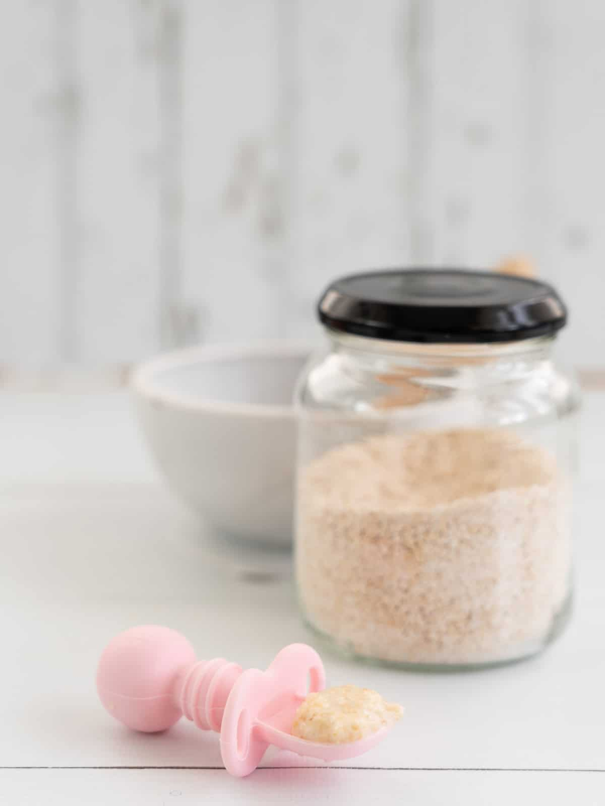spoonful of cooked baby porridge on a pink baby spoon with a jar of baby oats in the background