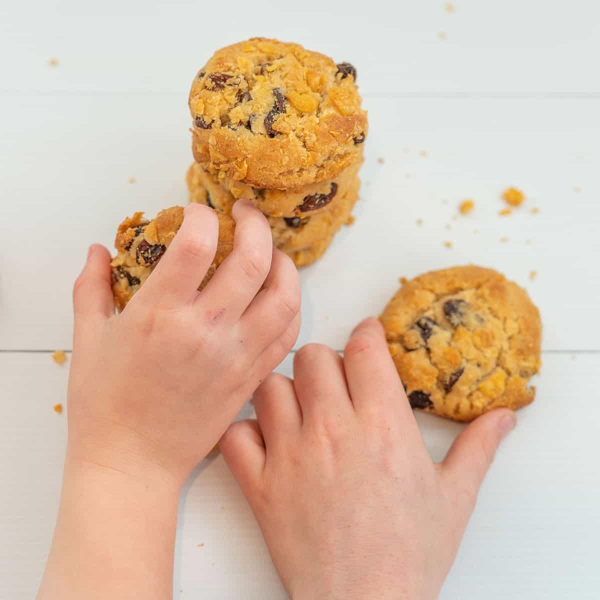 2 children's hands reaching for cornflake and raisin cookies