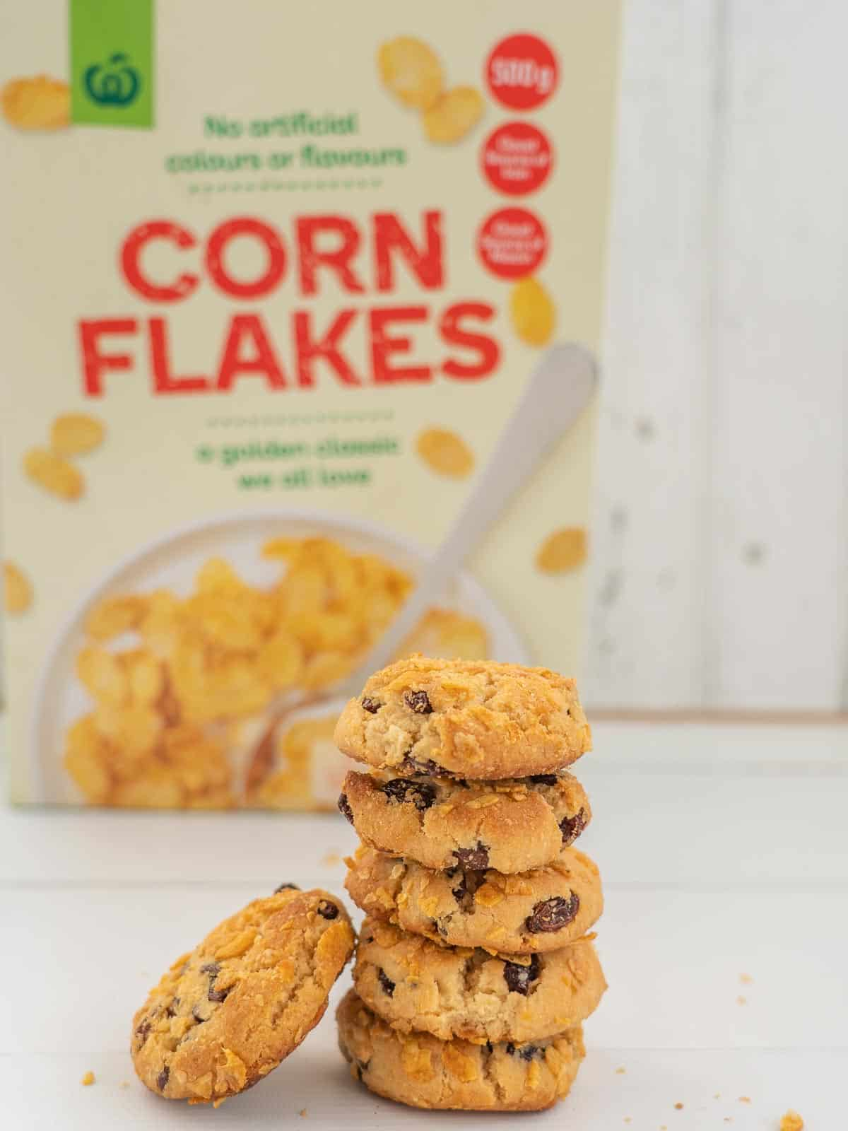 Stack of cookies sitting in front of a box of cornflakes