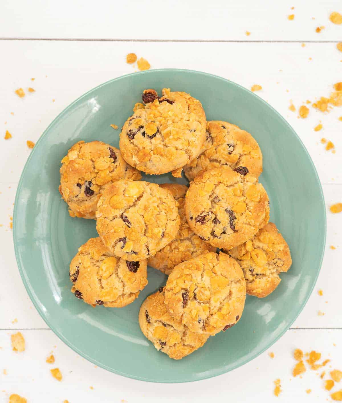 Cookies on a turquoise plate, cornflakes on the table top around the plate
