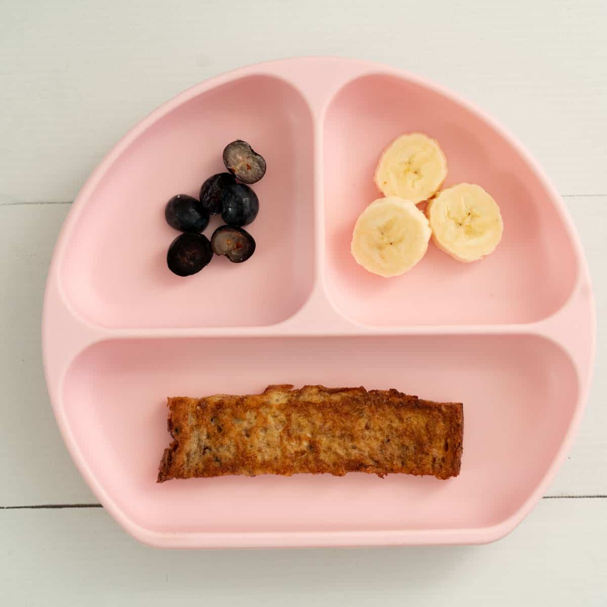 a pink baby breakfast plate with eggy bread, blueberries and sliced bananas