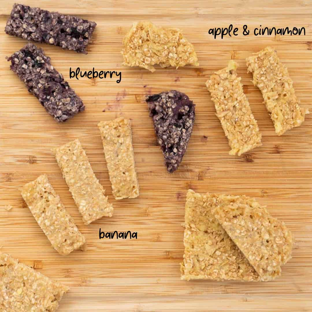 a selection of porridge fingers on a wooden board, apple and cinnamon, banana and blueberry
