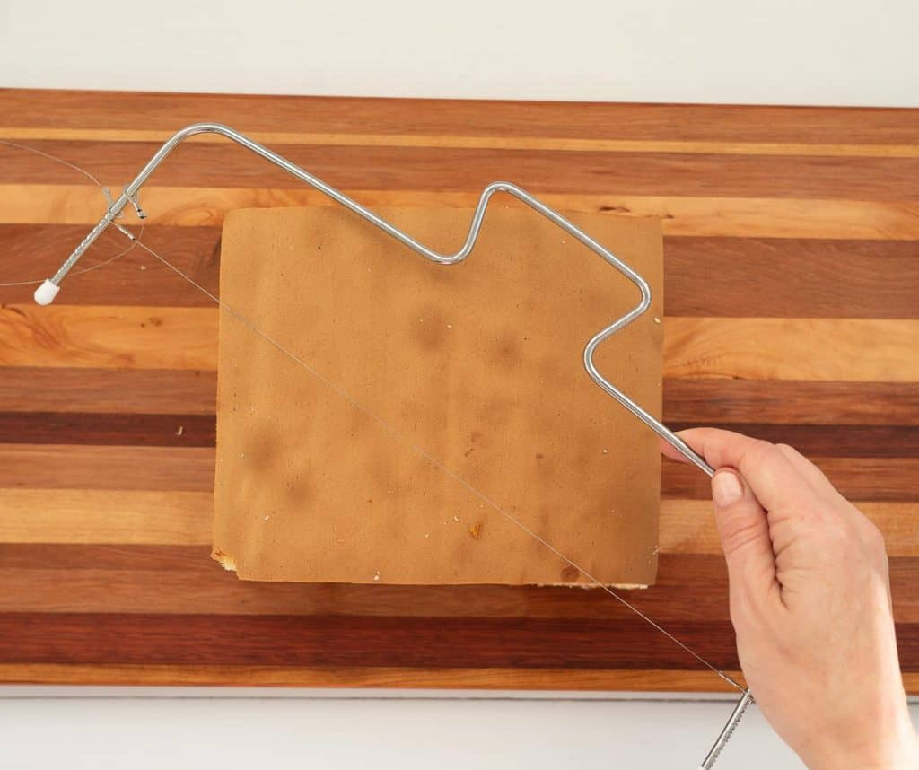 square sponge cake on a wooden chopping board with a cake leveler