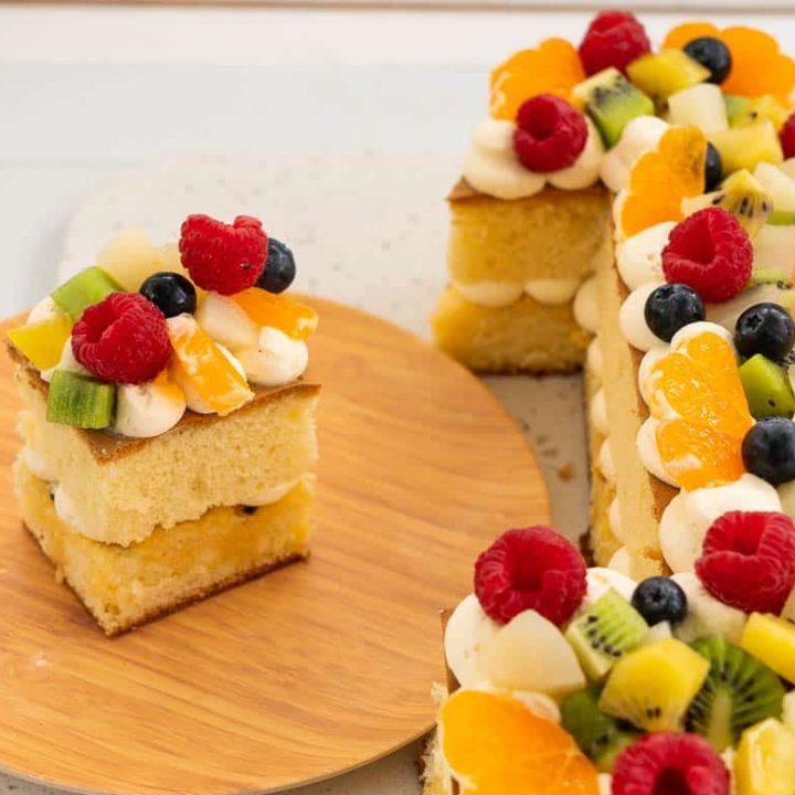 slice of fruit decorated cake next to a number 1 birthday cake