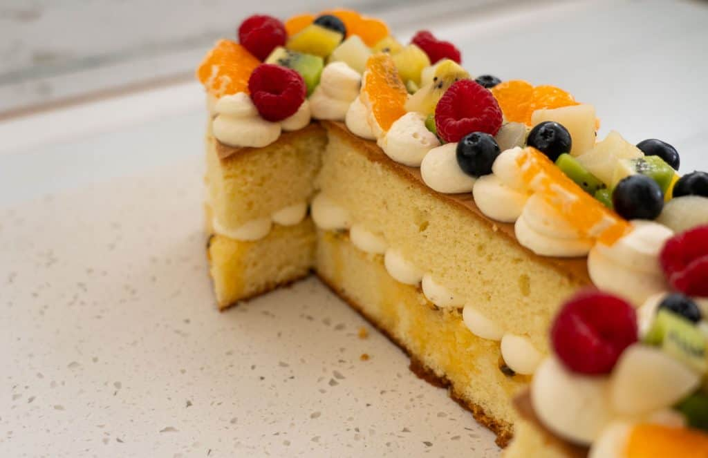 two layers of sponge cakes with piped whipped cream in the middle. The top of the cake is decorated with whipped cream and fruit