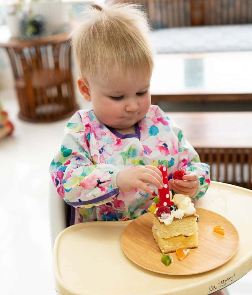 a baby in a high chair with a square fruit covered cake and a red number one candle