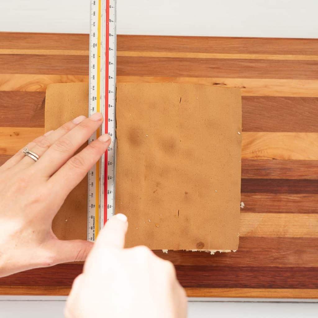 female hands cutting sponge cake using a ruler as a guide