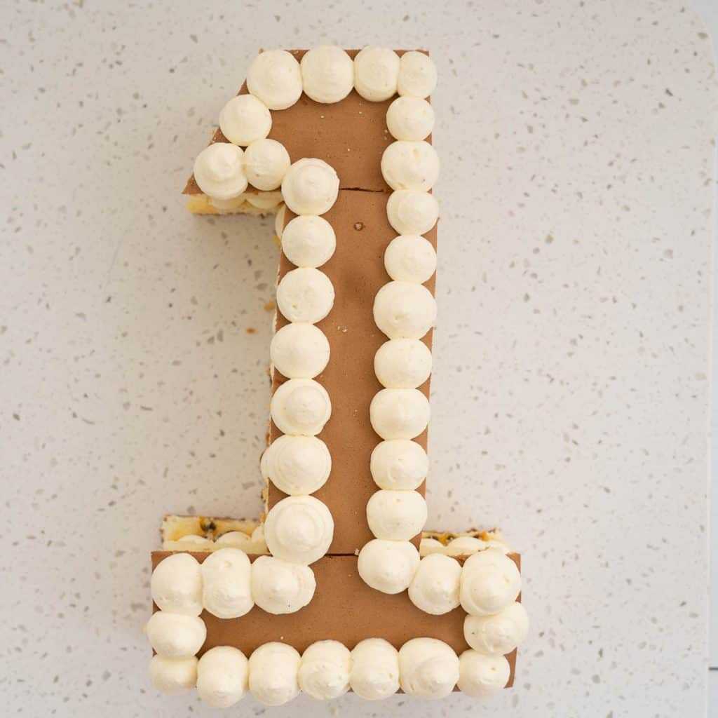 number 1 shaped birthday cake, decorated with whipped cream