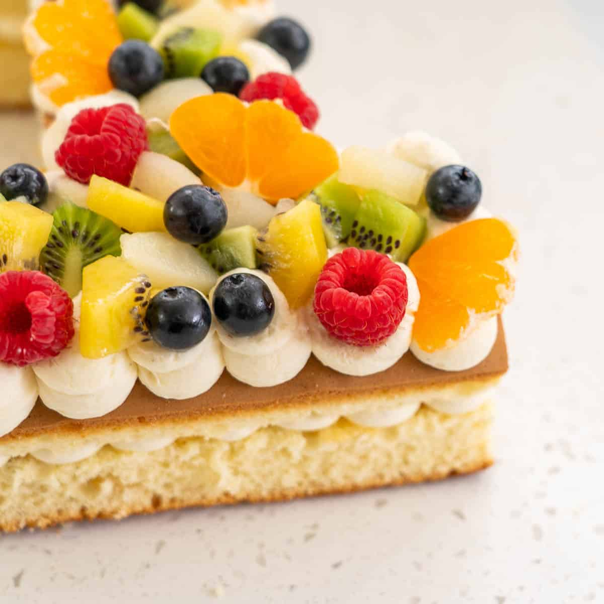 close up of fruit decorations on a birthday cake, raspberries, blueberries, kiwifruit, clementines