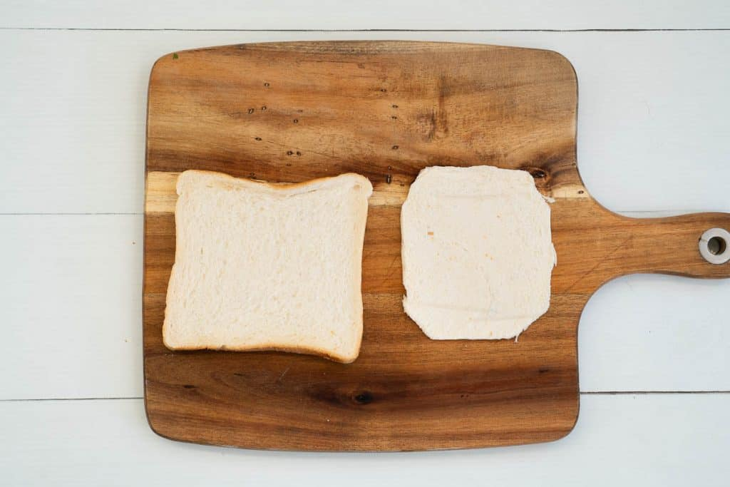 chopping board with 2 slices of bread, one has had the crusts removed and the corners trimmed