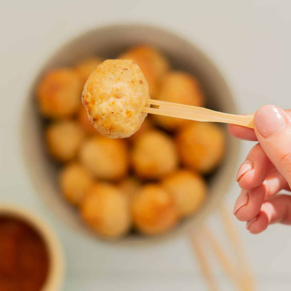 Chicken meatball on a bamboo fork being held above a bowl of meatballs