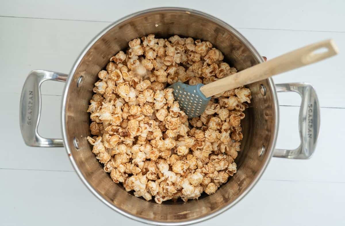 Popcorn with caramel sauce mixed through in a large saucepan